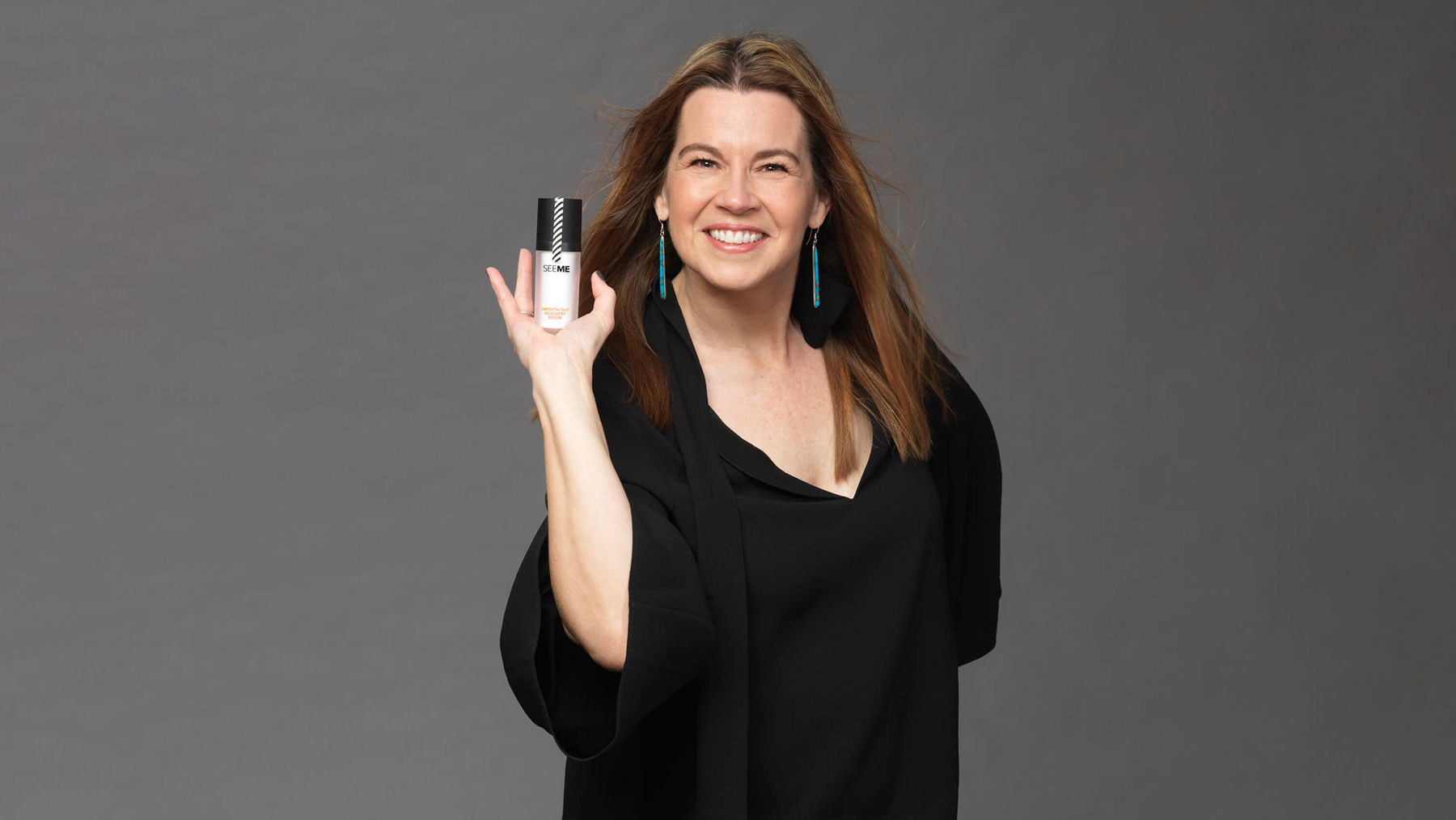 A menopausal aged woman holds a bottle of SeeMee Smooth Out Recovery Cream